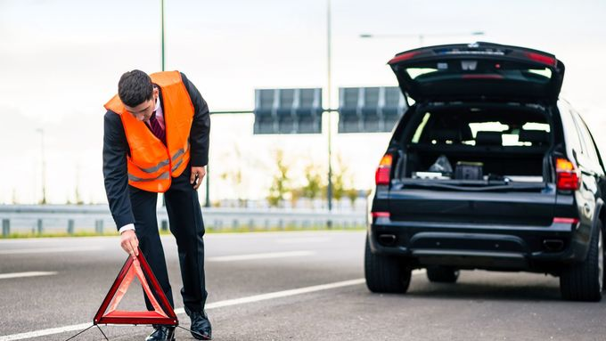Man with car breakdown erecting warning triangle